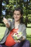 Νέα έγκυος προσφέροντας σαλάτα Στοκ Φωτογραφίες