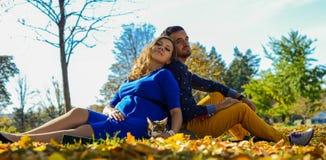 Νέα έγκυος συνεδρίαση ζευγών στα κίτρινα φύλλα στο πάρκο Στοκ φωτογραφία με δικαίωμα ελεύθερης χρήσης