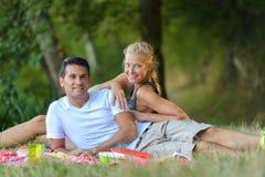 Νέα έγκυος χαλάρωση ζευγών στο πικ-νίκ στο πάρκο Στοκ φωτογραφίες με δικαίωμα ελεύθερης χρήσης