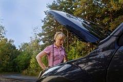 Νέα έκπληκτη γυναίκα που εξετάζει τη μηχανή αυτοκινήτων στοκ εικόνα με δικαίωμα ελεύθερης χρήσης