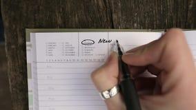 Νέα έναρξη από την έννοια Δευτέρας Νέο δημιουργικό κορίτσι που γράφει κάτω στο σημειωματάριό της για τα σχέδια απόθεμα βίντεο