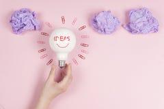 Νέα έννοια ιδέας με το τσαλακωμένο έγγραφο γραφείων, θηλυκή λάμπα φωτός εκμετάλλευσης χεριών Στοκ Εικόνα