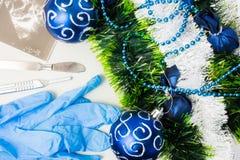 Νέα έτος και Χριστούγεννα στο depatment ή το χειρούργο χειρουργικών επεμβάσεων Τα προστατευτικά γάντια, τα χειρουργικά νυστέρια κ στοκ φωτογραφίες με δικαίωμα ελεύθερης χρήσης