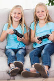 Νέα δίδυμα που παίζουν τα τηλεοπτικά παιχνίδια από κοινού Στοκ φωτογραφία με δικαίωμα ελεύθερης χρήσης