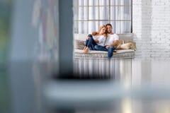 Νέα αγκαλιά ζευγών στον καναπέ Στοκ εικόνα με δικαίωμα ελεύθερης χρήσης
