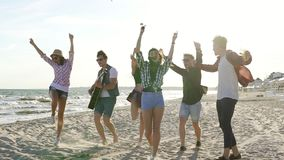 Νέα αγόρια και κορίτσια που χτυπούν, χορεύοντας τραγούδια κιθάρων μαζί παιχνιδιού και τραγουδιού σε μια παραλία στην άκρη νερού ` απόθεμα βίντεο
