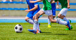 Νέα αγόρια που κλωτσούν το ποδόσφαιρο στον αθλητικό τομέα Παιδιά που τρέχουν με τη σφαίρα ποδοσφαίρου Στοκ φωτογραφίες με δικαίωμα ελεύθερης χρήσης
