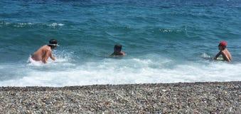 Νέα αγόρια που παίζουν στη θάλασσα στοκ φωτογραφία