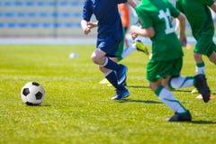 Νέα αγόρια που παίζουν τον αγώνα ποδοσφαίρου ποδοσφαίρου Στοκ Εικόνες