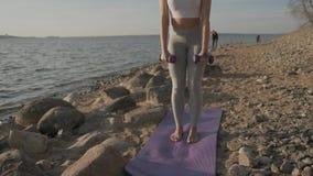 Νέα αθλητική όμορφη γυναίκα με τους αλτήρες στα χέρια στο υπόβαθρο της θάλασσας Κορίτσι ικανότητας που κάνει τις ασκήσεις με απόθεμα βίντεο