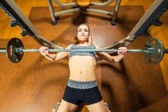 Νέα αθλήτρια που κάνει τις ασκήσεις με το barbell επάνω Στοκ φωτογραφία με δικαίωμα ελεύθερης χρήσης