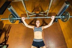 Νέα αθλήτρια που κάνει τις ασκήσεις με το barbell επάνω Στοκ Φωτογραφία