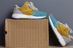 Νέα αθλητικά πάνινα παπούτσια, πάνινα παπούτσια ή εκπαιδευτές, σε ένα γκρίζο υπόβαθρο Στοκ Φωτογραφία
