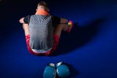 Νέα αθλητική αρσενική συνεδρίαση μπόξερ προς τα πίσω στο εγκιβωτίζοντας δαχτυλίδι Στοκ Εικόνα