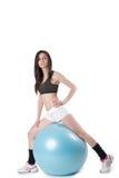 Νέα αθλητική γυναίκα που ασκείται με μια μπλε σφαίρα σταθερότητας στοκ εικόνες