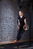 Νέα αθλητική γυναίκα που κάνει την άσκηση τράβηγμα-UPS με τα δαχτυλίδια ως σταυρό κατάλληλο workout ενάντια στο τουβλότοιχο Στοκ εικόνα με δικαίωμα ελεύθερης χρήσης