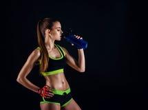 Νέα αθλητική γυναίκα sportswear με έναν δονητή στο στούντιο στο μαύρο κλίμα Ιδανικός θηλυκός αθλητικός αριθμός στοκ εικόνες