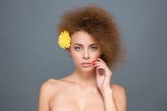 Νέα αισθησιακή σγουρή γυναίκα με το κίτρινο λουλούδι στην τρίχα της Στοκ Εικόνα