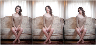 Νέα αισθησιακή συνεδρίαση γυναικών στη χαλάρωση καναπέδων Όμορφο μακρυμάλλες κορίτσι με την άνετη αφηρημάδα ενδυμάτων στον καναπέ Στοκ Φωτογραφία