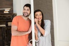 Νέα ακρόαση ζευγών μεταξύ τους μέσω της πόρτας στο σπίτι στοκ φωτογραφίες