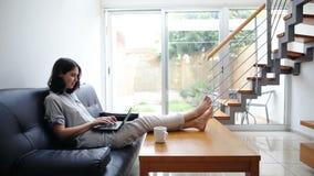 Νέα δακτυλογράφηση γυναικών στο lap-top στο άνετο σπίτι φιλμ μικρού μήκους
