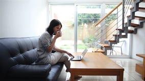 Νέα δακτυλογράφηση γυναικών στο lap-top στο σπίτι απόθεμα βίντεο