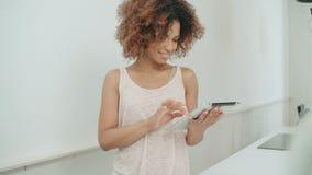 Νέα αμερικανική γυναίκα afro που χρησιμοποιεί την ταμπλέτα PC στο σπίτι απόθεμα βίντεο