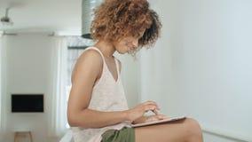 Νέα αμερικανική γυναίκα afro που χρησιμοποιεί την ταμπλέτα PC στο σπίτι φιλμ μικρού μήκους