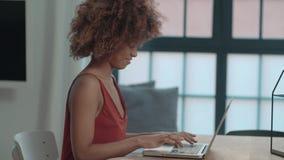 Νέα αμερικανική γυναίκα Afro που χρησιμοποιεί το φορητό προσωπικό υπολογιστή καθμένος στον πίνακα φιλμ μικρού μήκους
