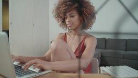 Νέα αμερικανική γυναίκα Afro που χρησιμοποιεί το φορητό προσωπικό υπολογιστή καθμένος στον πίνακα απόθεμα βίντεο