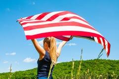 Νέα αμερικανική σημαία εκμετάλλευσης γυναικών στο υπόβαθρο μπλε ουρανού στοκ φωτογραφίες