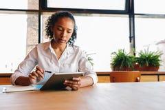 Νέα ανάγνωση γυναικών από την ψηφιακή ταμπλέτα Στοκ φωτογραφία με δικαίωμα ελεύθερης χρήσης