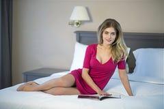 Νέα ανάγνωση γυναικών που χαλαρώνει διαβάζοντας στο κρεβάτι στοκ φωτογραφίες