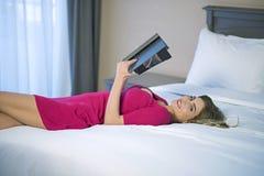 Νέα ανάγνωση γυναικών που χαλαρώνει διαβάζοντας στο κρεβάτι στοκ εικόνα με δικαίωμα ελεύθερης χρήσης