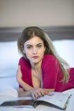 Νέα ανάγνωση γυναικών που χαλαρώνει διαβάζοντας στο κρεβάτι Στοκ εικόνες με δικαίωμα ελεύθερης χρήσης