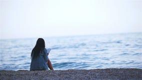 Νέα ανάγνωση γυναικών στην τροπική άσπρη παραλία φιλμ μικρού μήκους