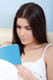 Νέα ανάγνωση γυναικών στο κρεβάτι Στοκ φωτογραφία με δικαίωμα ελεύθερης χρήσης