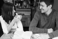 Νέα ανάγνωση ζεύγους και χαμόγελο στη καφετερία στοκ φωτογραφία