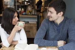 Νέα ανάγνωση ζεύγους και χαμόγελο στη καφετερία Στοκ εικόνες με δικαίωμα ελεύθερης χρήσης