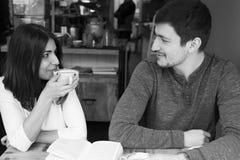 Νέα ανάγνωση ζεύγους και χαμόγελο στη καφετερία στοκ εικόνες
