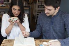 Νέα ανάγνωση ζεύγους στη καφετερία Στοκ εικόνα με δικαίωμα ελεύθερης χρήσης