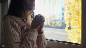Νέα ανίσχυρη γυναίκα που κοιτάζει μέσω του παραθύρου και που προσεύχεται, πίστη Θεών, μοναξιά απόθεμα βίντεο