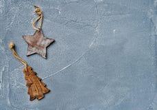 Νέα ανασκόπηση έτους ή Χριστουγέννων Αγροτικά ξύλινα αστέρι παιχνιδιών και δέντρο γουνών πέρα από την γκρίζα επιφάνεια grunge, το Στοκ Φωτογραφίες