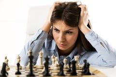 Νέα ανησυχημένη επιχειρηματίας μπροστά από τη σκακιέρα Στοκ Φωτογραφία