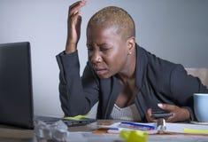 Νέα απελπισμένη και τονισμένη επιχειρησιακή γυναίκα αφροαμερικάνων που εργάζεται στο γραφείο φορητών προσωπικών υπολογιστών στο γ Στοκ εικόνα με δικαίωμα ελεύθερης χρήσης
