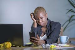 Νέα απελπισμένη και τονισμένη επιχειρησιακή γυναίκα αφροαμερικάνων που εργάζεται στο γραφείο φορητών προσωπικών υπολογιστών στο γ Στοκ Φωτογραφίες