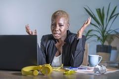 Νέα απελπισμένη και τονισμένη επιχειρησιακή γυναίκα αφροαμερικάνων που εργάζεται στο γραφείο φορητών προσωπικών υπολογιστών στο γ Στοκ Εικόνες