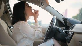 Νέα αρκετά κομψή συνεδρίαση επιχειρησιακών γυναικών brunette σε ένα σταθμευμένο κραγιόν αυτοκινήτων και χρωμάτων, που χρησιμοποιε φιλμ μικρού μήκους