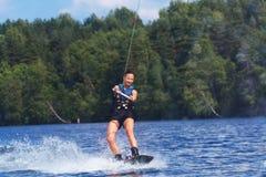 Νέα αρκετά λεπτή γυναίκα brunette που οδηγά wakeboard στο κύμα του mot Στοκ Εικόνες