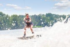 Νέα αρκετά λεπτή γυναίκα brunette που οδηγά wakeboard στο κύμα του mot Στοκ Φωτογραφίες